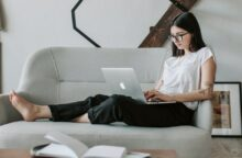 A woman sits on a couch with her laptop in her lap.