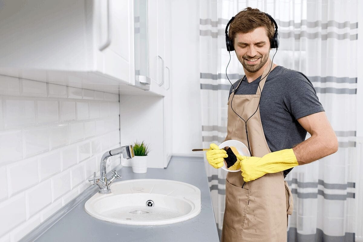 Man listening to music while doing dirty dishes in the kitchen with no dishwasher in apartment